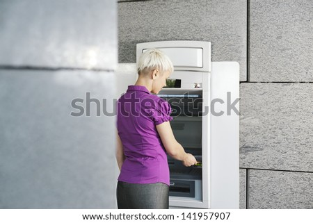 business woman withdrawing cash at bank atm - stock photo