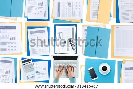 Business woman working at desktop on a laptop with financial reports, paperwork and files, top view, unrecognizable person - stock photo