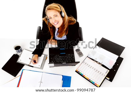 Business woman working at her desk, happy and smiling as she multitasks - stock photo