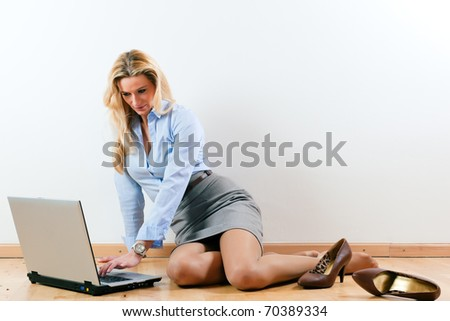 Business woman working at home with her laptop on the floor - stock photo