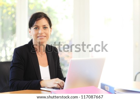 Business woman working on a laptop at office - stock photo