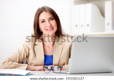 Business woman working on laptop computer at office - stock photo