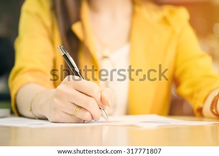 business woman working with document and laptop in office vintage tone - stock photo
