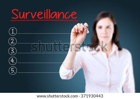 Business woman writing blank Surveillance list.Blue background. - stock photo