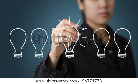 Business Woman writing Light Bulb Outstanding concept - stock photo