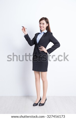 business woman writing something on white wall background, great for your design or text, asian - stock photo