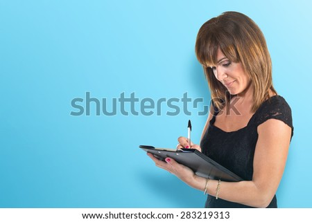 Business woman writting a document over colorful background - stock photo