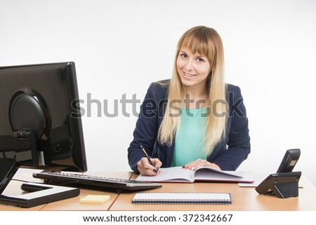 Business woman wrote in a notebook and looked into the frame - stock photo