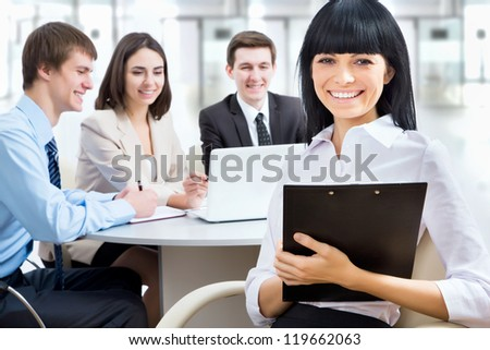 Business womanl holding a folder and looking at camera with a smile - stock photo