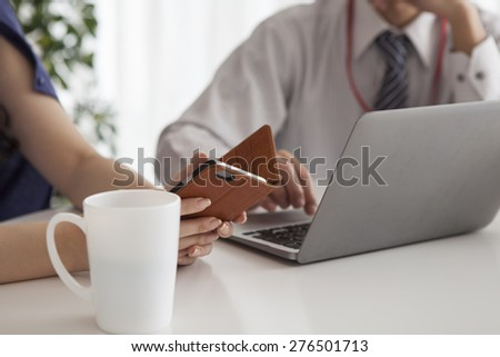 Business women and businessman look at the laptop screen - stock photo