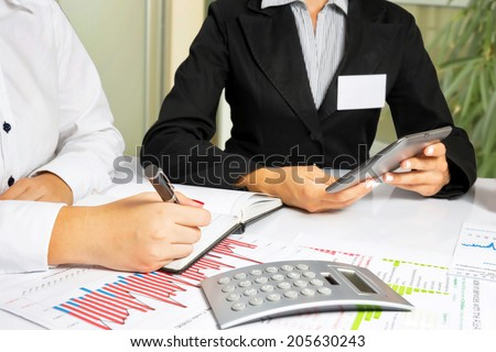 Business women doing annual report, at office desk. - stock photo