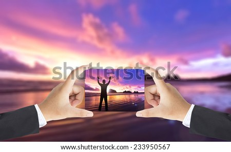 Business women hands holds picture silhouette of man with hands raised to beautiful sunset compare with the actual location.The sunset on the Pak Meng Beach, Trang Thailand. - stock photo