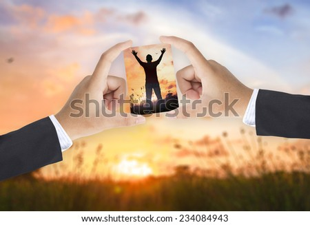 Business women hands holds picture silhouette of man with hands raised to beautiful sunset compare with the actual location. - stock photo