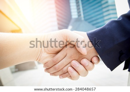 Business women handshake on bright background - stock photo