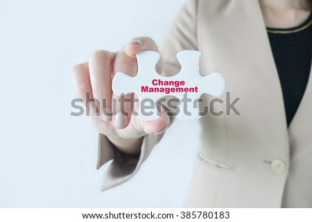 Business women holding a piece of jigsaw puzzle with word Change Management - stock photo