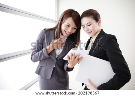 Business women look and smile conversation with computer and digital tablet in Office, asian - stock photo