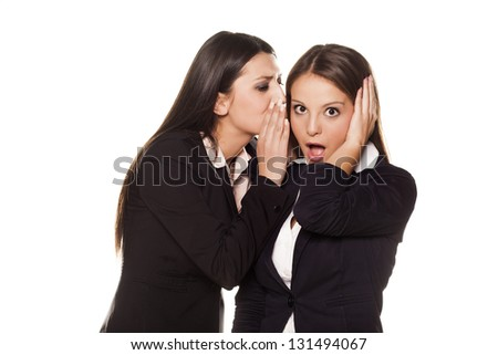 business women whispering to his colleague on her ear - stock photo
