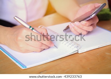 Business women writing and working on desk office. - stock photo
