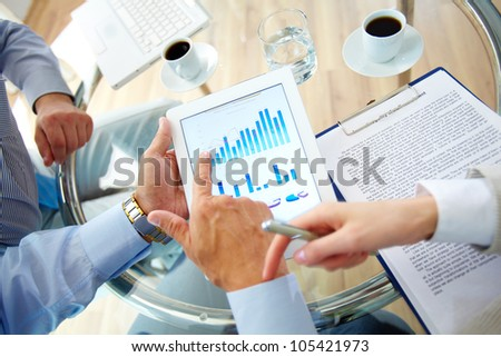 Business work-group analyzing financial data to develop new strategy - stock photo