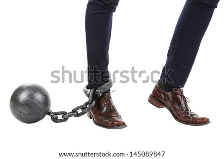 Business worker with ball and chain attached to foot isolated on white - stock photo