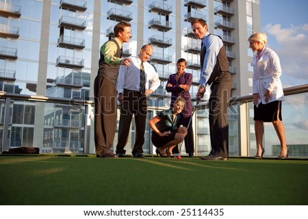 Business workers playing golf outside office, having fun - stock photo