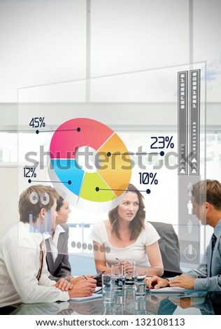 Business workers using colorful pie chart interface in a meeting - stock photo