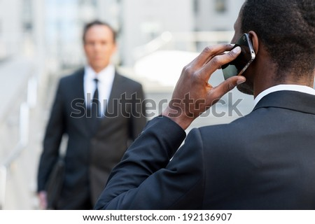 Business world. Rear view of African man in formal wear talking on the mobile phone while another businessman walking on background - stock photo