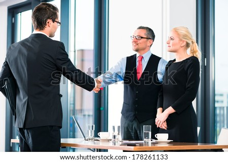 Business - young man in job interview for hiring, welcomes, Boss or Senior and his female Assistant in their office - stock photo