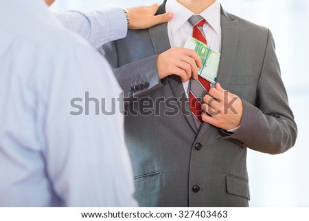 Businessman accepting bribe money and putting it in his pocket while another businessman taps him on the shoulder. - stock photo