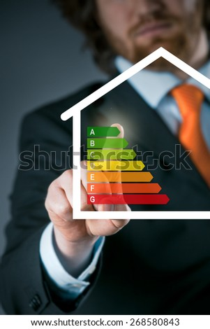 Businessman activating an energy efficiency chart on a virtual interface conceptual of an efficient eco friendly energy and temperature setting on a modern smart house - stock photo