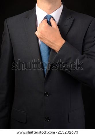 Businessman adjusting his tie - closeup shot  - stock photo