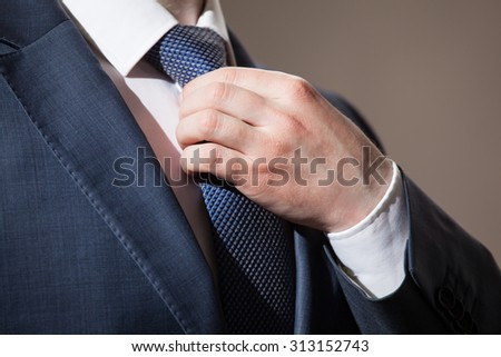 Businessman adjusting his tie - closeup shot - stock photo