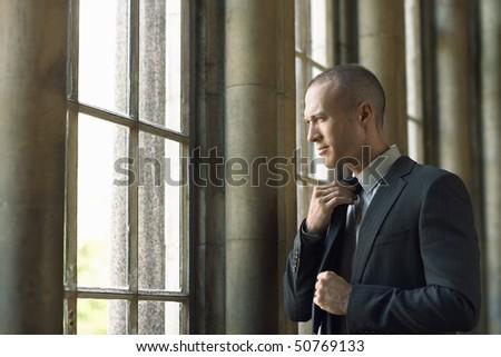 Businessman Adjusting Tie by window - stock photo