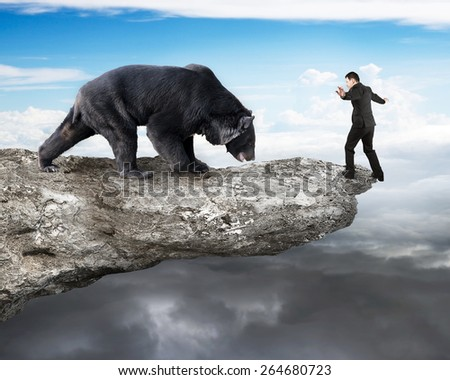 Businessman against black bear balancing on cliff with sky cloudscape background - stock photo