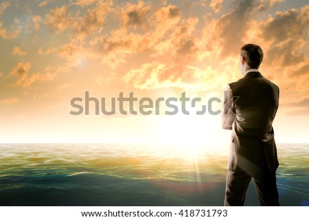 Businessman against sea in morning light, rear view - stock photo
