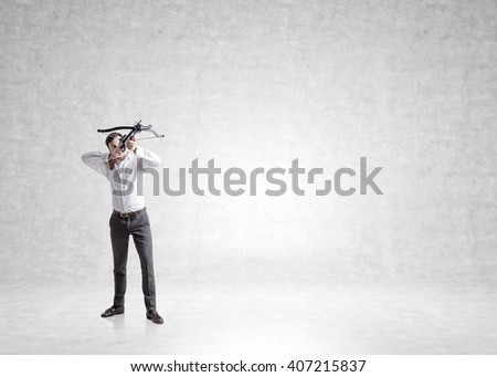 Businessman aiming at target with bow and arrow on concrete wall background. Mock up - stock photo
