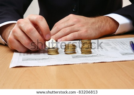 Businessman allocating  coins on the stock chart diagram - stock photo