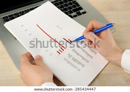 Businessman analyzing charts, closeup - stock photo