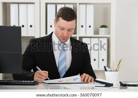 Businessman analyzing financial charts at desk in office - stock photo