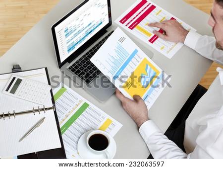 Businessman analyzing financial report - stock photo