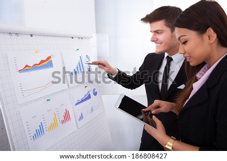Businessman analyzing graph while female colleague using digital tablet in office - stock photo