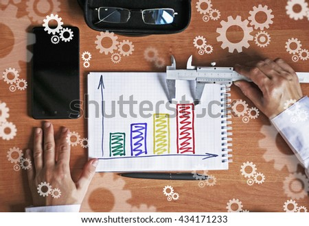 Businessman analyzing investment charts with notepad caliper - stock photo