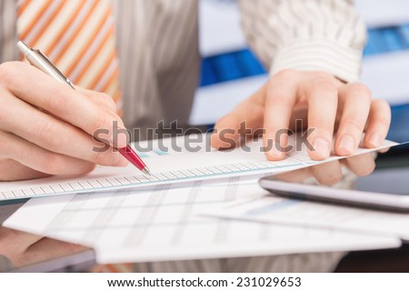 Businessman analyzing report at office, desk with papers close-up - stock photo
