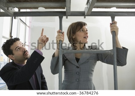 Businessman and a businesswoman looking at their new office - stock photo