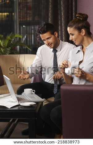 Businessman and assistant discussing work at hotel lobby by coffee table. - stock photo