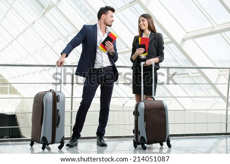 Businessman and business woman communicating to the flight at airport - stock photo