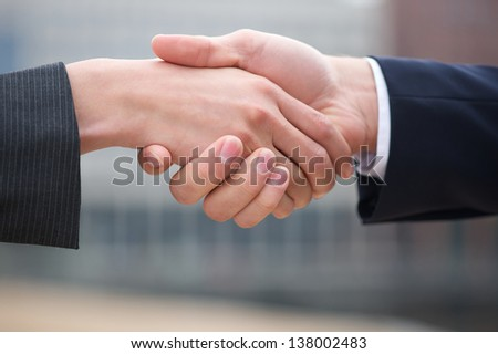 Businessman and business woman handshake close up - stock photo