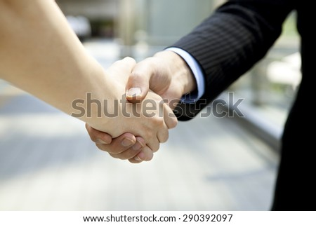 Businessman and business woman shaking hands in street - stock photo