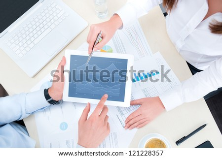Businessman and businesswoman analyzing financial report on a modern digital tablet. Top view shot. - stock photo