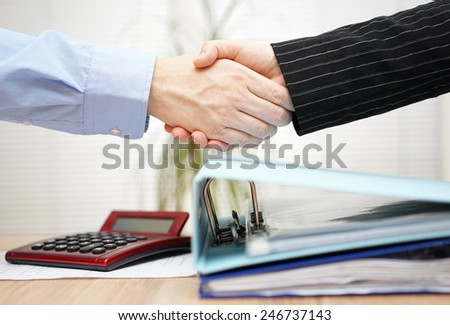 businessman and businesswoman are handshaking over binders - stock photo